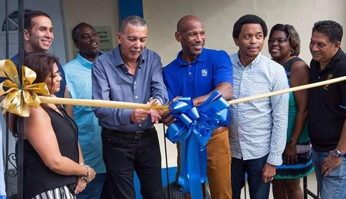 President Anthony Carmona, fourth from left, gets some assistance from RBC's managing director Darryl White, fourth from right, as he cuts the ribbon to officially open Presentation College San Fernando new squash court on Saturday. Photo: EDISON BAKER