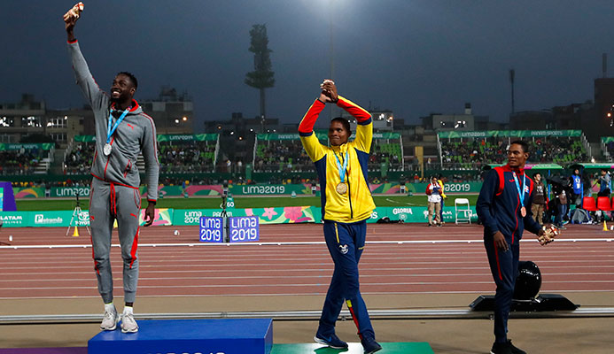 Silver medalist Jereem Richards of Trinidad and Tobago, right, walks away as gold medalist Alex Quinonez of Ecuador, center, and bronze medalist Yancarlos Martinez of Dominican Republic celebrate on the podium for the men's 200m during the athletics at the Pan American Games in Lima, Peru, Friday, Aug. 9, 2019. (AP Photo/Moises Castillo)